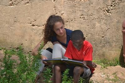 A care volunteer reads to a child in Jamaica