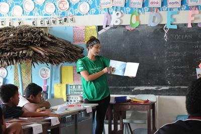 Projects Abroad Care volunteer reads a book to a class at her placement in Samoa