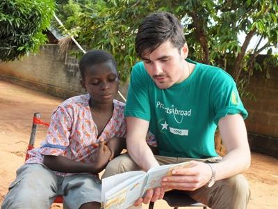 A Projects Abroad volunteer reads with a young boy during a Care project in Togo