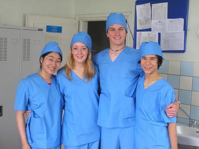 Teen Medicine volunteers dressed in scrubs in a hospital abroad